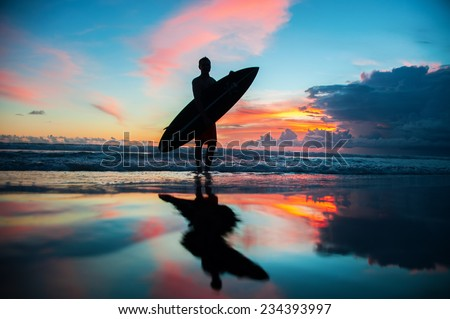Young surfer with board on the beach