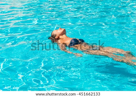 Young tanned woman in bikini swims in swimming pool