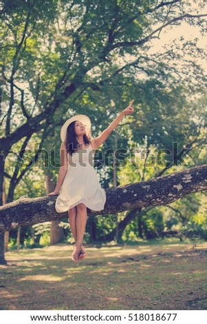 Young teen girl sitting on tree