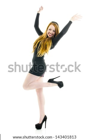 Young teenager girl wearing a elegant short black dress and black high heels and dancing, stetching her arms up in the air isolated against white background.