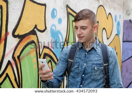 Young teenager with her cell phone and near of a wall painted with graffiti