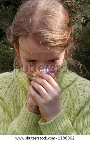 Young, thoughtful girl smelling crocuses