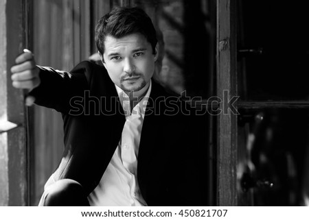 Young thoughtful handsome stylish man with beard wearing black fashionable suit sitting near old grunge window with wooden frame in dark loft interior