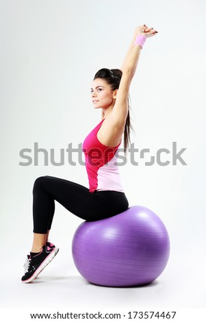 Young thoughtful sport woman stretching on fitball on gray background