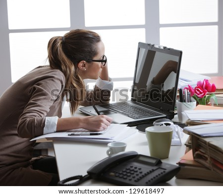 Young tired businesswoman with tons of documents