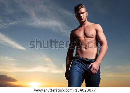 young topless man outdoor looking down at the camera, with the sunset behind