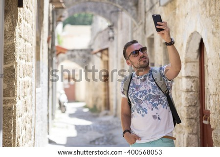 young tourist taking pictures with mobile phone