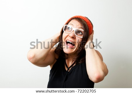 Young trendy woman scared, holding her head screaming. Studio shot.