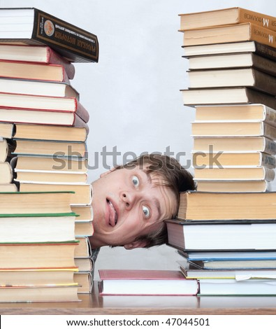 Young unhappy student with one's tongue hanging out and stacked books