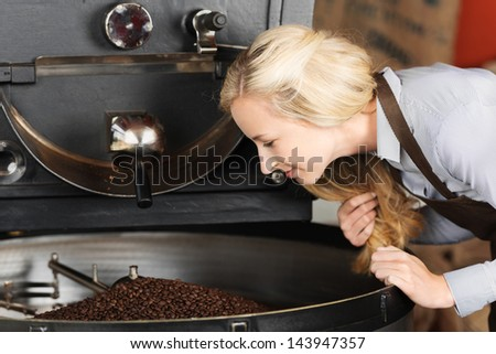 Young waitress smelling coffee beans in cooling container at cafe