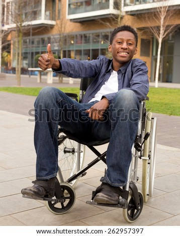 young wheelchair user showing the thumbs up symbol