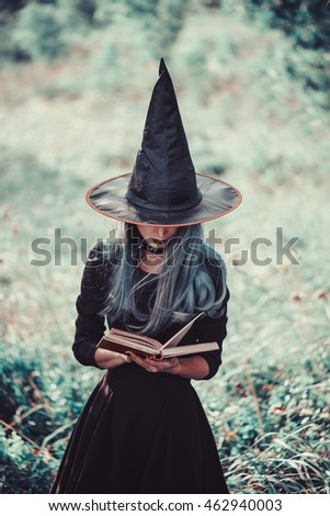Young witch reading book of magic in the forest. Toned Image