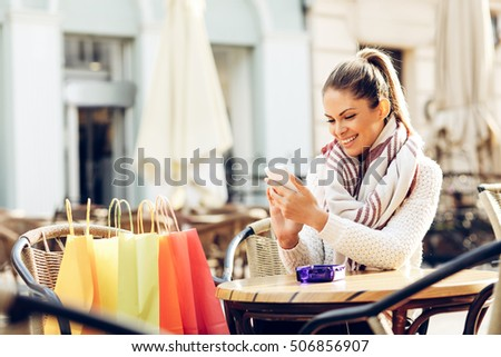 Young woman after shopping typing message on phone in cafe