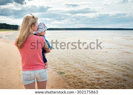 young woman and baby at the beach near sea
