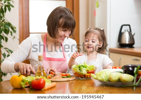 Young woman and her child daughter making vegetable salad