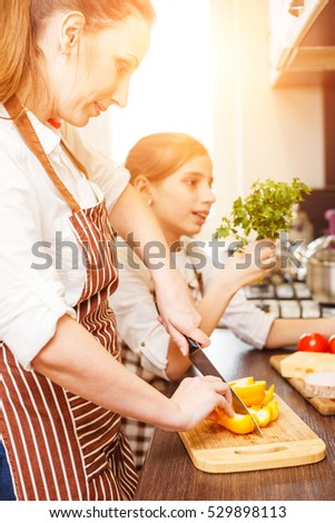 Young woman and her daughter cooking together in the kitchen. Teenage girl with her mom having fun at family cooking