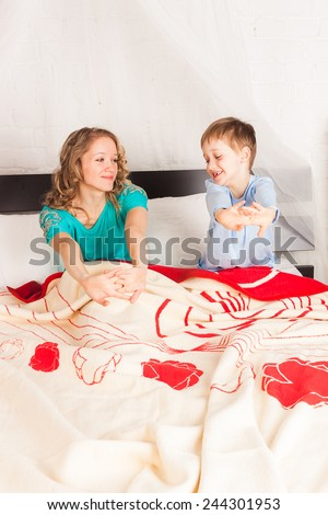 Young woman and her son waking up in big bed