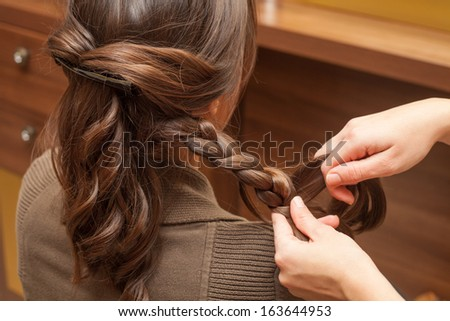 young woman at hairdresser making braid of hair