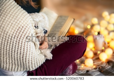 Young woman at home reading book with dog on her knees. Winter holiday concept