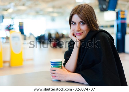 Young woman at international airport, drinking coffee while waiting for her flight. Female passenger at terminal, indoors.