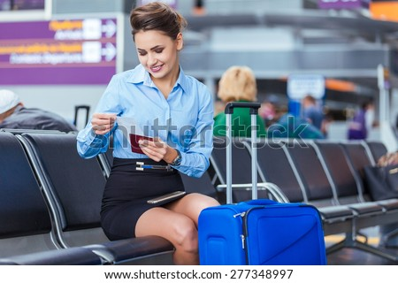 Young woman at international airport, sitting while waiting for flight. Female passenger at terminal, indoors.