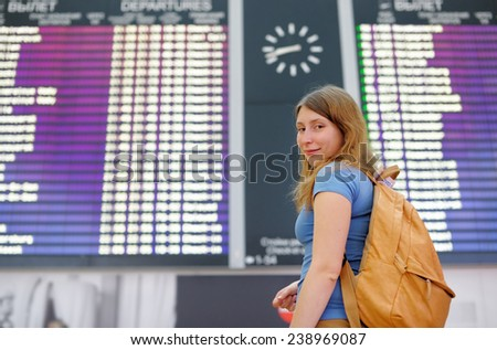 Young woman at the international airport, with flight board on background