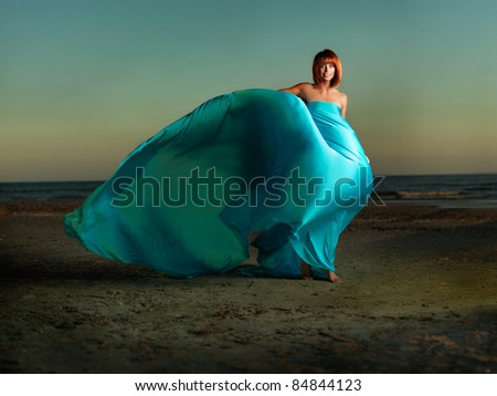 young woman beach turqouise dress wind blowing