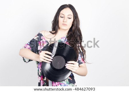 Young woman bending a vinyl record, trying to breaking it. Indoors, over a grey background.