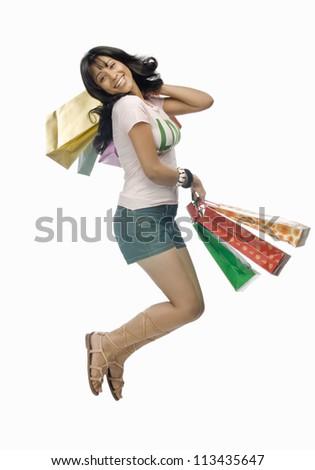 Young woman carrying shopping bags and jumping