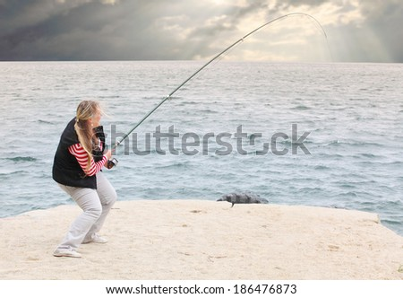 Young woman catching fish.