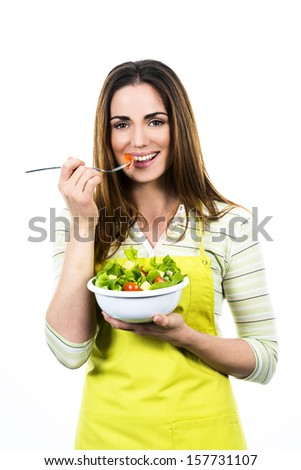 Young Woman Cooking and eating healthy Food - Vegetable Salad. Diet. Dieting Concept. Healthy Lifestyle. Cooking At Home. Prepare Food