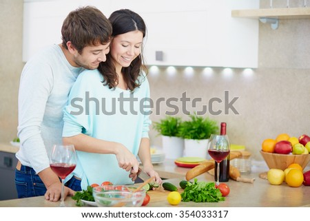 Young woman cooking salad in the kitchen with her husband near by