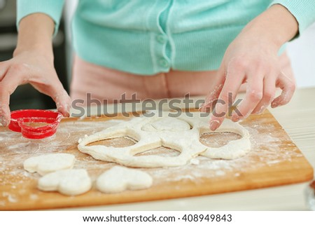 Young woman cutting out the hearts in a dough on the kitchen counter