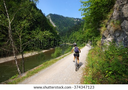 Young woman cycling along Dunajec river - Poland