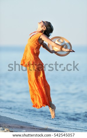 young woman dancing on the beach in summer