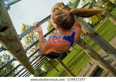 Young woman doing Australian Pull-ups on a jungle gym.
