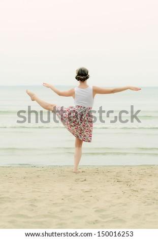 Young woman doing dancing elements near the sea