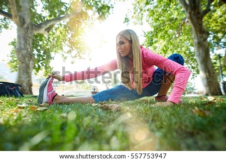 Young woman doing morning workout exercises in citypark after running, sunlight.