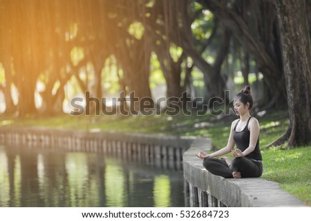 Young woman doing yoga in morning time with the sun lighting in the park with pond