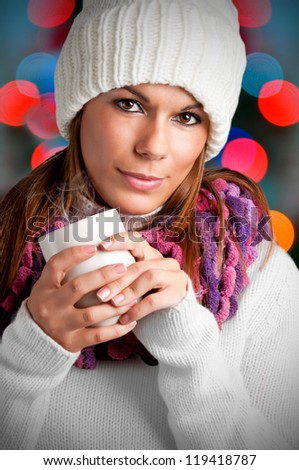 Young woman drinking a hot drink from a white mug