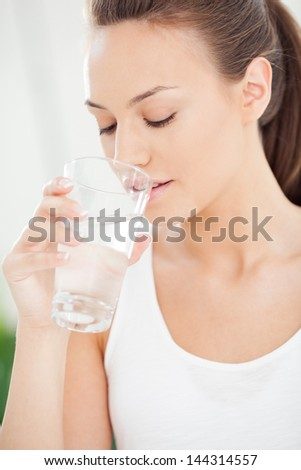 Young woman drinking fresh water.