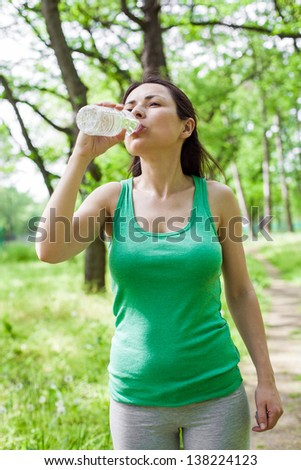 Young woman drinking water at park after exercising