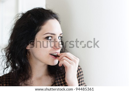 Young woman eating chocolate against white background