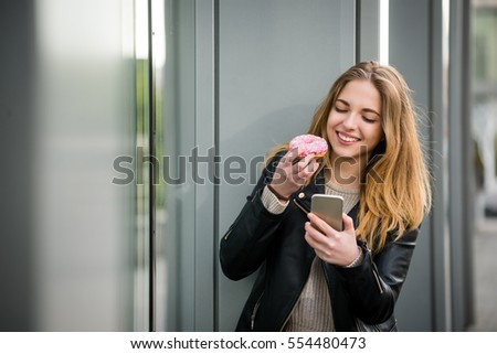 Young woman eating tasty donut and looking to phone outside in street