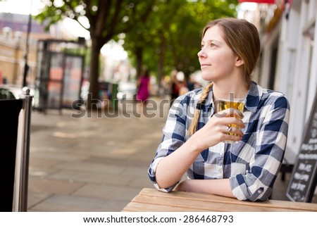 young woman enjoying a beer outside a bar