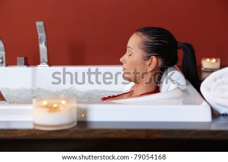Young woman enjoying wellness bubble bath with eyes closed in candle light.?