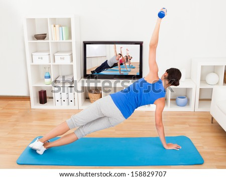 Young Woman Exercising On Mat In Front Of Television