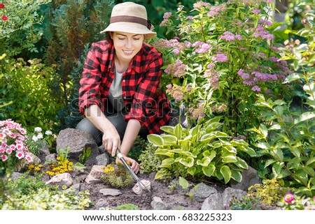 young woman gardener care of flowers in the garden people gardening care of