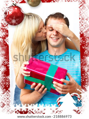 Young woman giving a present to her husband against christmas themed frame