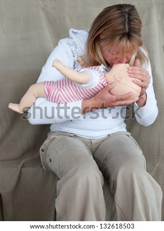 Young woman giving CPR to an infant